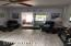 Large living room with gray laminate flooring, ceiling fan, additional lighting and walk out to back patio