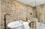 Beautiful stacked stone, stand alone tub, and limestone shower
