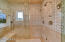 The steam shower offers mosaic tile work on the walls and basket weave marble on the floor.