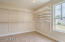 Large walk-in closet with window for natural lighting.