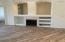 Spacious great room with fireplace built-in bookshelves, tile wood plank floors.