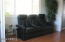 The living room accommodates seating perpendicular to a couch and opposite it.