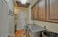 Large separate laundry room with uppers and sink with base cabinet storage