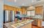 Kitchen with cedar cabinets, stainless appliances and stylish backsplash