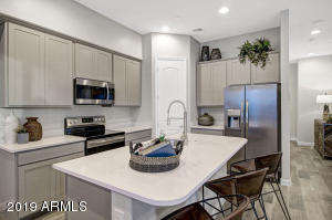 Gorgeous kitchen with walk-in pantry and stainless steel appliances. Photo represents model home.