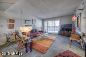 Spacious living room with south facing balcony is light & bright.