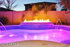 Night time view of pool with dramatic fire bar and water features!