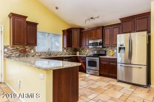 Refreshed Kitchen with slab granite and cherry cabinetry.