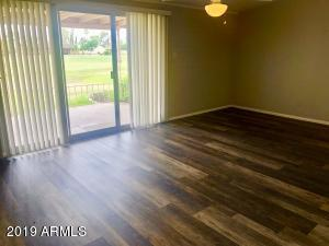 Spacious Living room with lighted ceiling fan and views of the North Golf Course. New flooring in 2018!!