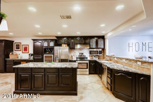 Large fully updated kitchen features island, wine chiller and abundant cabinetry and lighting, all open to view