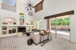 Family room has soaring vaulted ceilings, sliding door to covered back patio and a gas fireplace