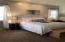 Large airy bedroom with many windows and French doors to private covered patio