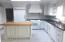 Butcher block island with vegetable sink, stone counter tops.