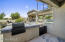 The outdoor kitchen has a two grills, a sink and beverage cooler.