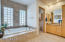 Master Bathroom with His/Her Sinks, Vanity, Jetted Tub, Water Closet, Walk in Shower with Rain Shower Head and Walk in Closet.