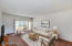 Virtually staged great room with exterior access to the covered patio/balcony.
