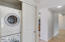 Stacked washer/dryer next to bedrooms.
