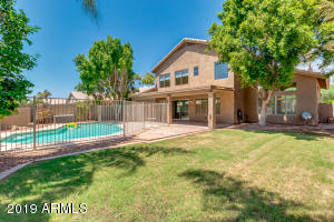 A Resort Style backyard boasts a HUGE Sparkling Fenced Pool! Multiple seating areas around the pool for perfect entertaining! The extended covered patio overlooks lush green grass and mature landscaping.