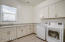 Large laundry with granite counters, and upper and lower cabinetry.