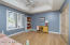Second bedroom with natural wood flooring and coffered ceiling