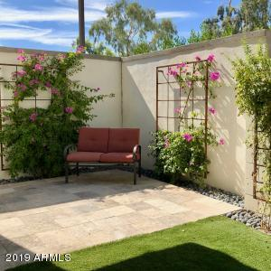 Beautifully landscaped backyard boasts synthetic grass for very little maintenance.