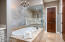 Elegant soaking tub, spacious step-in shower, linen closet