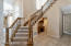The staircase features wood handrails and balusters. There is a built-in desk tucked just underneath the staircase too!