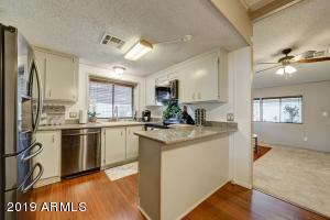 Kitchen w/ Granite Countertops, Stainless Steel Appliances, Laminate Wood Flooring.