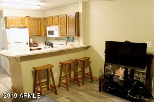 Walk in and see the laminate flooring leading into the kitchen with a breakfast bar