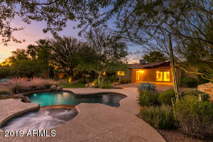 YOUR BACKYARD PARADISE AWAITS! Sitting on a 17,000+ sqft lot, this beautiful 4B/3B split floor plan home is an entertainer's dream! Enjoy mountain views while sitting next to your outdoor fireplace, or relaxing in the salt water pool and hot tub. Lighted paths lead you to tranquil areas to sit and read a book. Don't forget about inside! With fresh interior paint and new carpets, this move-in ready home features 2 living areas, a fire place, and an extra large utility room with wine refrigerator and extra refrigerator. Retreat to your oversized master bedroom with reclaimed Phoenix Suns court wood floors! You don't want to miss your chance to own a piece of sports history and one of the largest lots in the neighborhood!