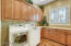 Cabinets with crown molding, wood floors, sink, plantation shutters