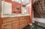 2 sinks with granite vanity,tile floor, shower/tub with granite surround
