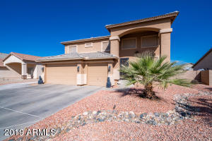 Front of house with 3 car garage and low maintenance desert landscaping