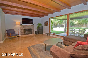 Great room with amazing wood beamed ceiling and floor to ceiling windows to backyard.