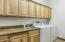The perfect pristine oversized laundry room with an abundance of cabinetry.