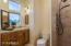 Travertine shower and vanity with knotty Alder