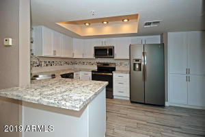 Upgraded kitchen with granite counters, white cabinets, backsplash and stainless steel appliances