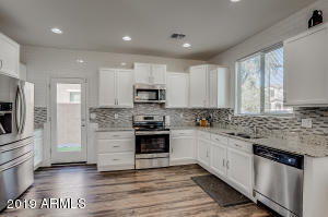 Kitchen featuring stainless steel appliances, to-the-ceiling subway tile, granite, back splash, walk-in pantry, and open concept!