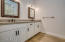 Double sinks in the second master home with quartz countertops and shaker cabinets.
