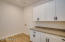The laundry room has plenty of cabinet space for storage
