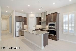 Kitchen features a gas cooktop, stainless steel appliances, granite countertops, walk in pantry and bar.