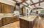 Gourmet kitchen is spacious and features granite counters, prep sink, gas cooktop, high end appliances, and an additional full-size refrigerator in the butler's pantry.