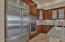 Gourmet kitchen featuring GE Monogram appliances & leaded glass cabinetry.