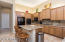 Kitchen with granite countertops, electric cooktop, wall ovens, island and walk-in pantry