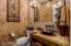 Exquisite powder room w/custom sandstone slab counter & bronze vessel sink.