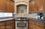Gourmet kitchen with Custom Hood, Frigidaire, LG and Bosch Stainless Appliances and granite Countertops and Kitchen Island