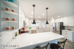The Remodeled Kitchen is the center of the Home featuring modern NEW shaker cabinetry, gorgeous white Quartz, modern subway tile backsplash, SS Appliances, chef's sink and faucet with custom pendant lighting over the HUGE breakfast bar.