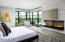 Master suite overlooks pool and lush yard.