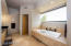 Chic master bath with spa tub, horizontal window for lighting and privacy.