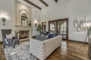 The formal living has a gas fireplace, beamed ceiling and doors to a private patio.